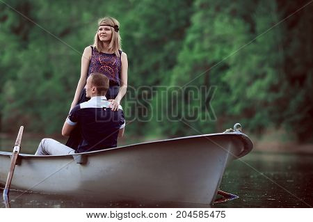 young guy and girl hugging in the white boat, handsome man and beautiful woman enjoying outdoor recreation, happy teenager looking at nature