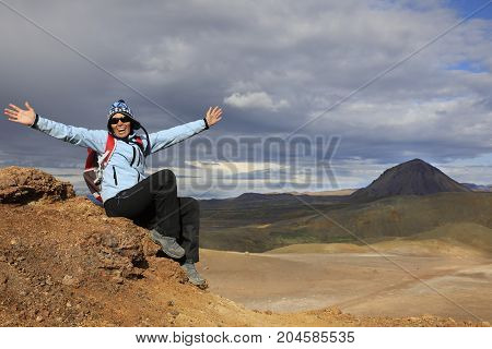 Girl in waterproof clothing sits on the cliff with happy outstretched arms amid the vast expanses of Iceland
