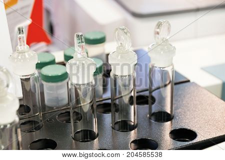 Glass test tubes in a metal holder. Laboratory equipment. Shallow depth of field.