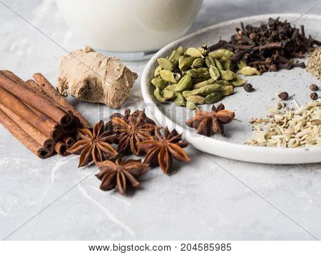 Ingredients for masala tea - milk, cinnamon, cardamom, anise, fennel, ginger, black tea, star anise, black pepper, cloves on grey background.