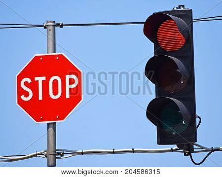 Stop sign and red light at the road crossing