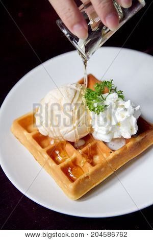 Belgian waffles with vanilla ice cream and syrup on white dish