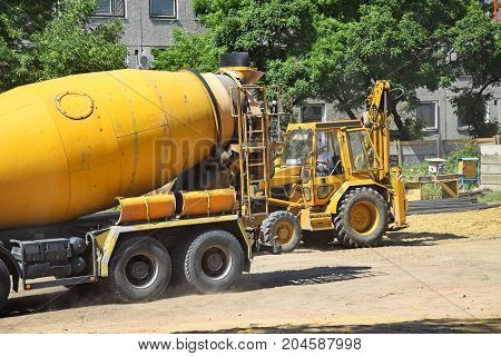 Cement mixer and excavator at the construction site