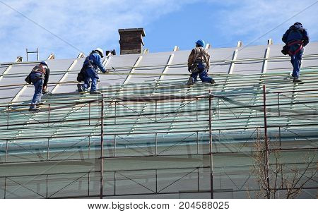 Roofers are working on the roof of a building