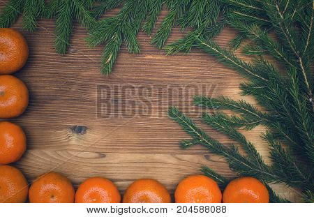 Tangerines and christmas tree branches on burnt wooden surface background with copy space. Christmas background.