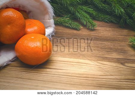 Tangerines scaterred from Santa Claus hat and christmas tree branches on burnt wooden surface background with copy space. Christmas background.