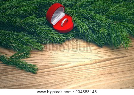Wedding ring in heart shape box in Christmas tree branches on burnt wooden table background. Marriage Proposal.