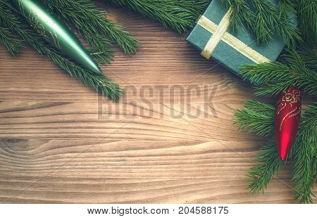 Christmas present box in fir tree branches with toy icicles on burnt wooden table surface background with copy space.