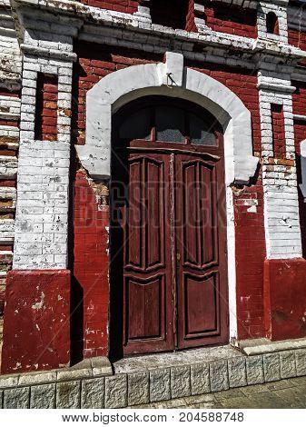 Old door in an old building. Ancient architecture. Brown door. Red door. Wooden door.