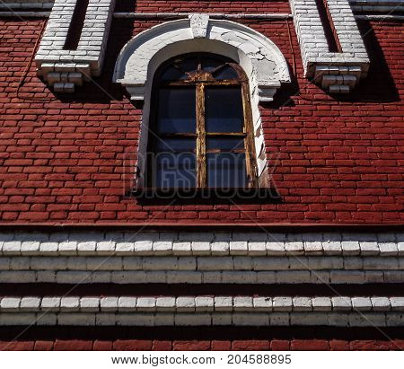 Old window in an old building. Ancient architecture. Old window. Window. Red wall. Architectural decor.