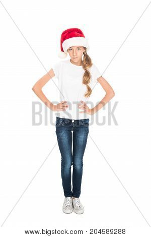 dissatisfied female teenager posing in casual clothes and Santa hat isolated on white