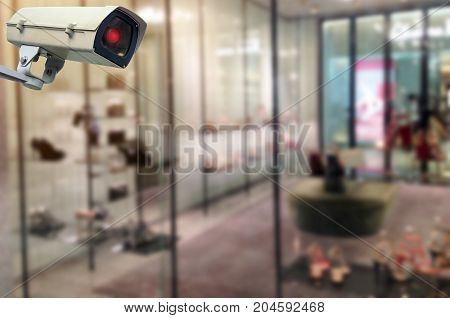 CCTV security indoor camera system operating at trendy shoes shop in department store shopping mall fashion shopping surveillance security and safety technology concept