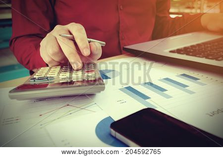 young man calculate finances about cost with calculator laptop smart phone and business strategy diagram report on desk at home office income and expenses money cost savings and economy concept