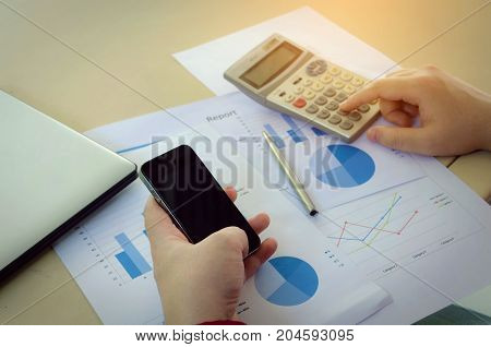 hand working with finances about cost and calculator mobile smart phone business strategy diagram report and laptop computer on desk at home office income and expenses money cost savings concept