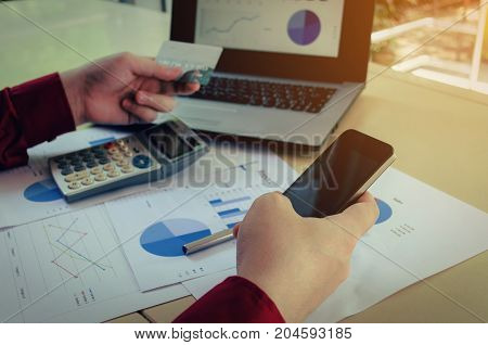 hand paying with credit card and entering security code with mobile smart phone laptop and income and expenses strategy diagram report on desk at home office payment and shopping online concept