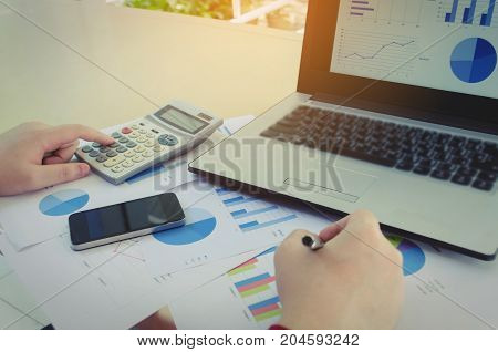hand working with finances about cost and calculator business strategy diagram report laptop computer on desk at home office income and expenses money cost savings and business economy concept