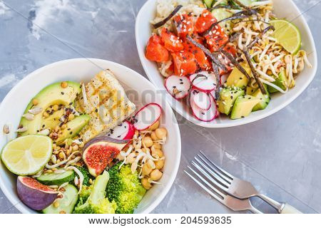 healthy lunch buddha salad bowls ahi poke. concrete background healthy vegan trend food concept.