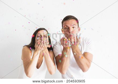 Young man and woman blowing confetti decorations on white background