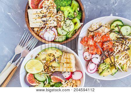 healthy lunch buddha salad bowls ahi poke. concrete background healthy vegan trend food concept.