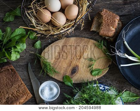 Ingredients for breakfast - fresh eggs in a wire basket, fresh greens - spinach, dill and green onions, salt, rye bread. rustic style. Top view