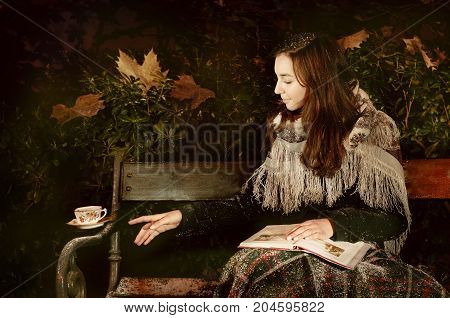 Caucasian cute girl with book and levitating tea cup on a park bench