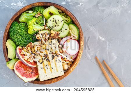 buddha bowl with tofu broccoli and vegetables in a wooden bowl. vegan healthy food concept.