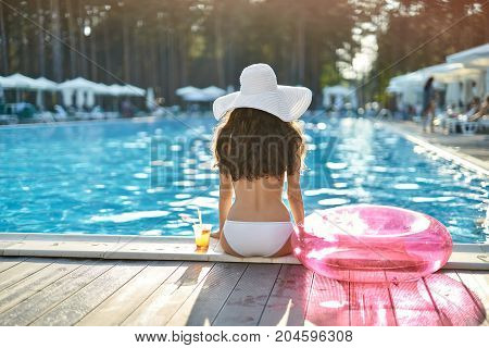 Cute girl in a white swimsuit with a hat sits on the pool's edge outdoors. Next to her there is a glass with a cocktail and a pink swim ring. Shoot from the back. Horizontal.