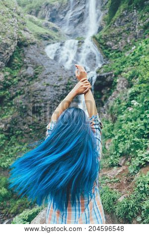 Tourist young woman with blue hair standing with raised arms in front of waterfall concept of travel and freedom.