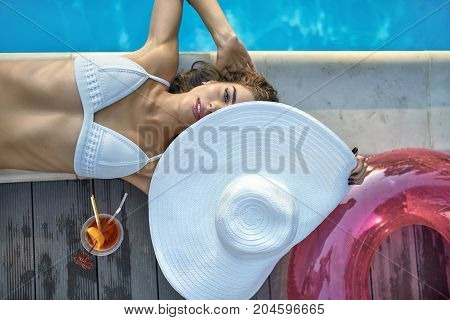 Glad girl in a white swimsuit lies on the pool's edge outdoors. She holds a big hat which partially closes her face and looks into the camera with parted lips. Top view horizontal photo.