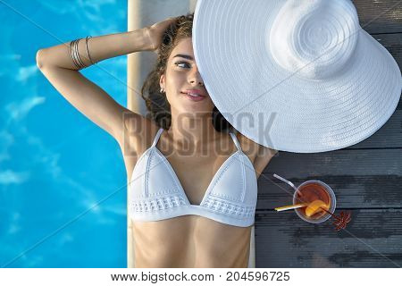 Cute girl in a white swimsuit lies on the pool's edge outdoors. She holds a big hat which partially closes her face and looks to the side with a smile. Next to her there is an orange cocktail.