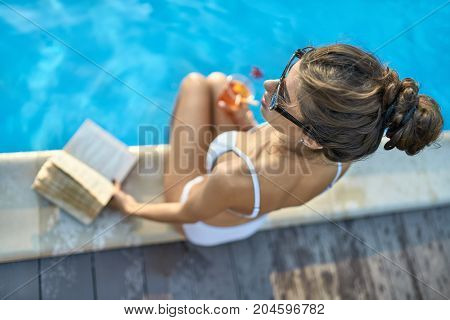 Beautiful girl in a white swimsuit and sunglasses sits on the pool's edge outdoors. She holds a book and an orange cocktail. Top view low aperture horizontal photo. Closeup.