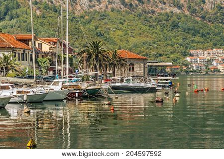 Fishing boats and small yachts on the water near the seaside village. Bay of Kotor (Adriatic Sea), Montenegro.