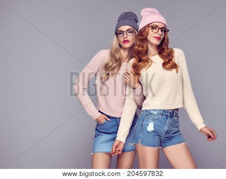 Fashion. Pretty Sisters Best Friends Twins. Young beautiful woman in Stylish Autumn Winter Outfit. Cool Hipster Model in Cozy sweater, Glamour glasses. Playful Blond Redhead Girls in Trendy Beanie hat