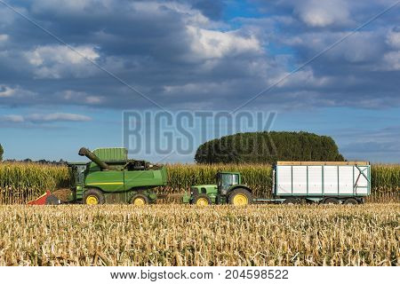 Combine Harvester Corns Followed By A Tractor With The Trailer
