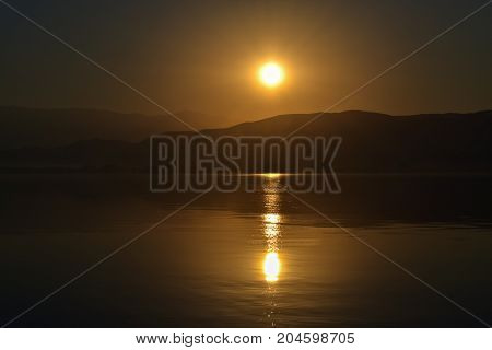 Beautiful summer sunset over the sea and reflection in the water