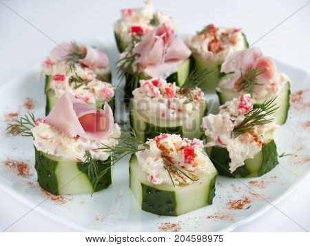 Stuffed cucumbers with cheese cream from smoked cheese with garlic crab sticks greens and ham top