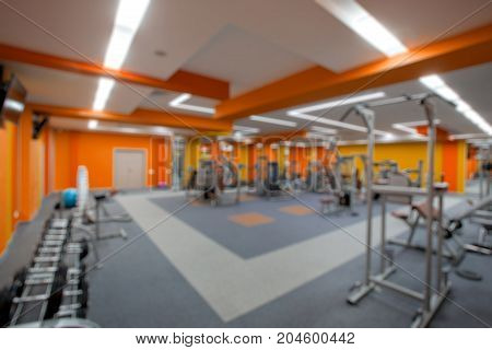 Blur abstract background modern fitness center lifestyle with health exercise equipment: Blurry perspective view gym facility service room: Empty gymnasium indoor space for diet, bodybuilding training.