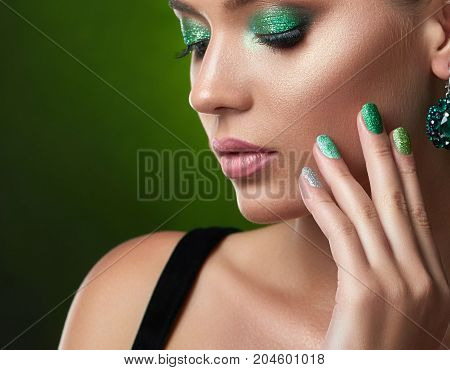 Close up of pretty sensual brunette girl with perfect bronze skin, shiny manicure, long eyelashes, makeup in green colors, touching face. Beautiful woman with closed eyes, big rounded earring posing.