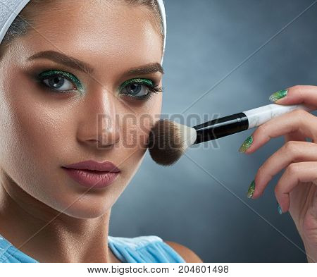 Close up of pretty confident woman with green makeup, bronze skin holding ankle, drawing blush for herself. Concept of professional makeup, care about face, beauty salon. Dark background.
