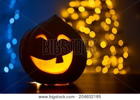 Smiling pumpkin with one tooth and big eyes, decorated and prepared for Halloween, sitting on wooden table in shadow. Blue background with yellow lights. Celebrating autumn holiday.