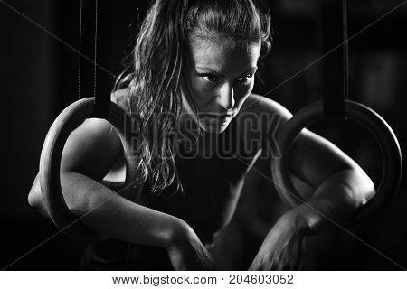 Woman Athlete Exercising On Gymnastic Rings, Black And White Image, Black Background