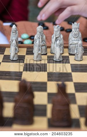 Closeup of Artistic Chess Pieces on Wooden Board: Strategy and Leadership Concept Game