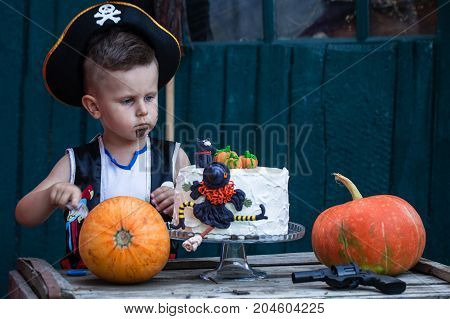 A little pirate with a pumpkin and a festive cake