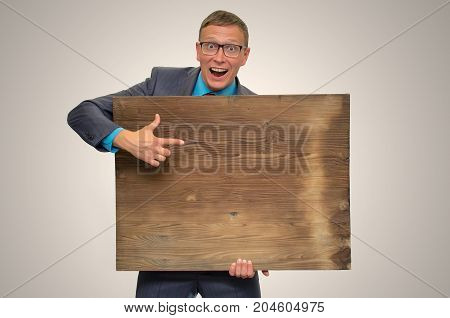 Funny smiling business man in suit and glasses holding in hands empty bill board with copy space and showing by finger on it. Advertisement board. Product presentation.