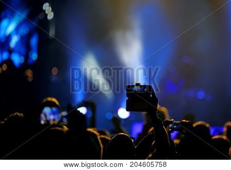 fans who take pictures and record videos with modern smartphones during the live concert of a rock band on stage