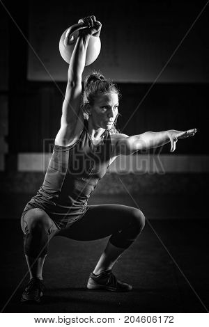 Woman Athlete Exercising With Kettlebell, Black And White Image, Black Background\
