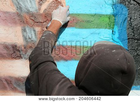 young writer with dirty painted sweatshirt painting a wall