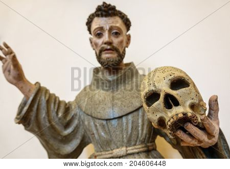 Closeup of wooden holy figure holding skull with woodworm, focus on skull