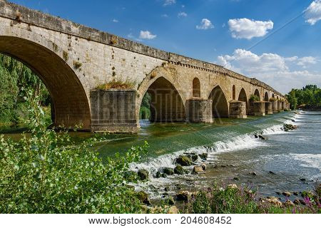 Wide angle view of bottom of Tordesillas antique bridge over Duero river