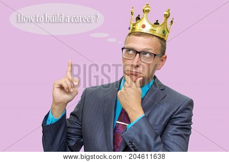Young caucasian business man in suit and glasses and with golden crown above his head keeps his finger on his chin and thinking about How to build a career. Career ladder. Success.